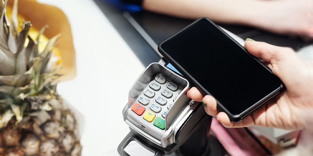 person pays for groceries with phone