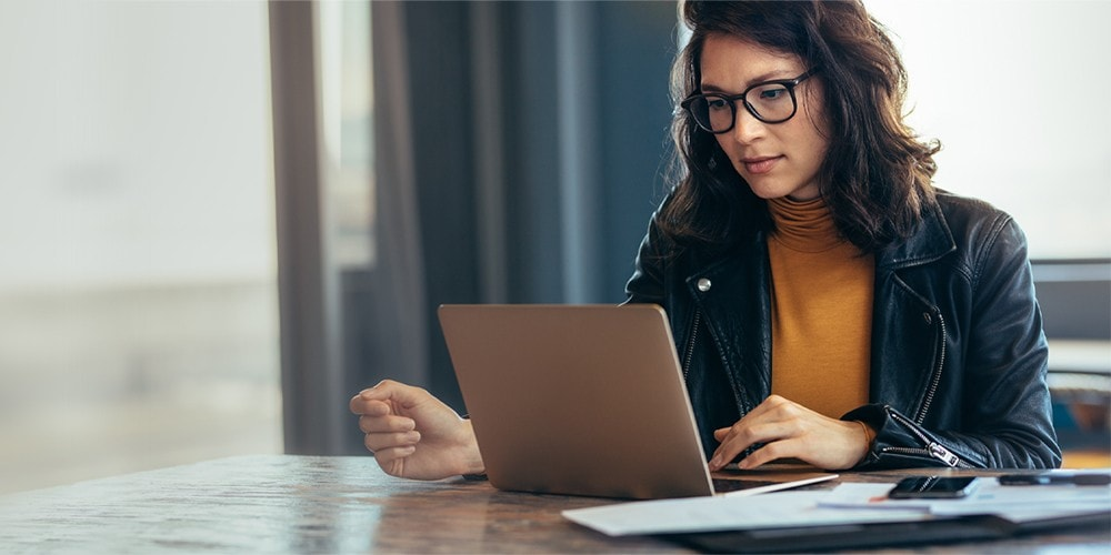 Woman in glasses sits at table looking at laptop